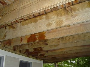 Deck floor joists held up by deck ledger board at house.